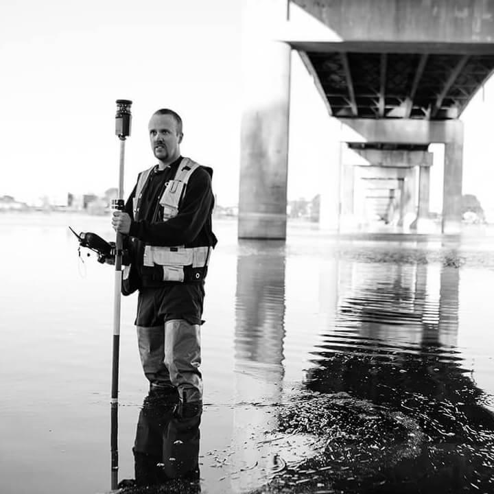 Arpenteur de Denicourt qui prend une mesure sous un pont