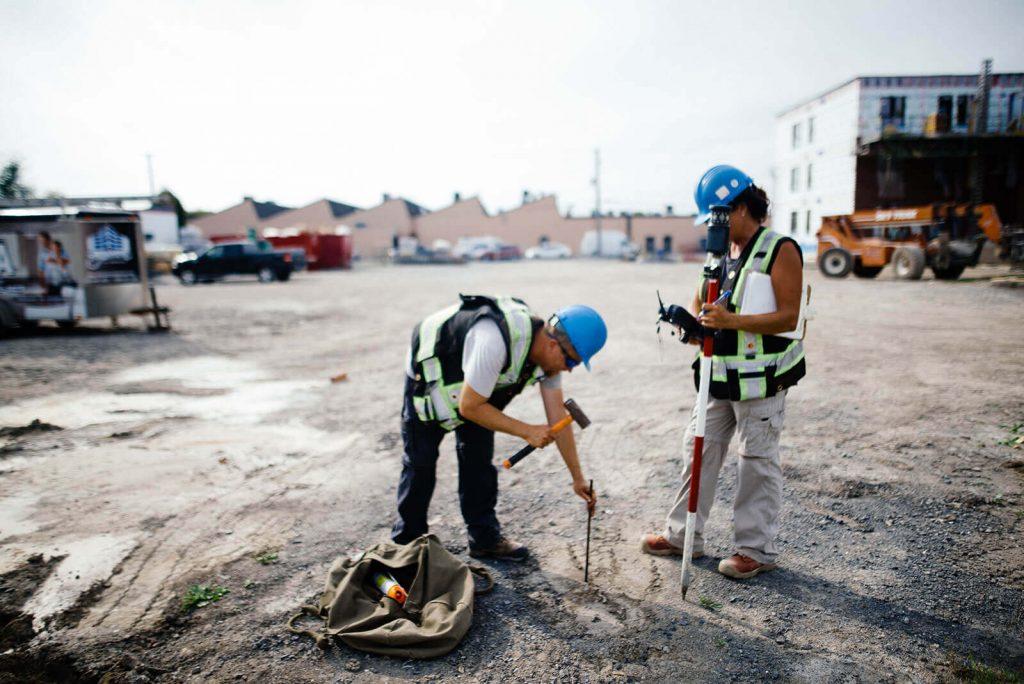 deux travailleurs en arpentage qui pique un terrain